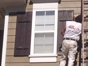 Man Removing Brown Window Shutter - Cumming, GA - Exterior Painting Project - Kimberly Painting Contractor