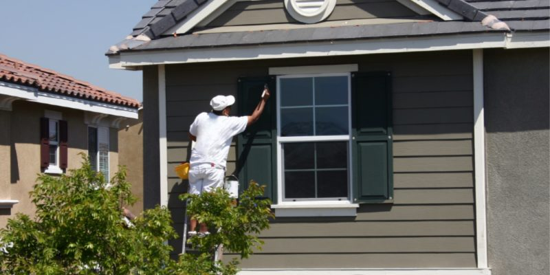 Exterior Painting Techniques - Kimberly Painting - Sandy Springs, GA - Painter on ladder painting shutters gray